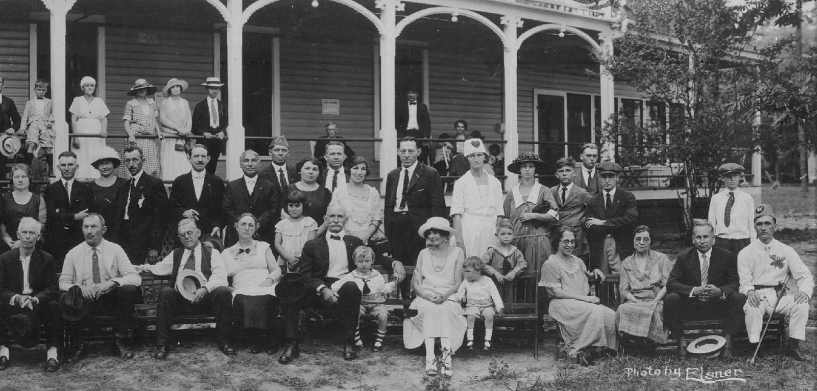 Residents of the early Moosehaven, along with family members, pose on the front porch of Bradon Hall. Black and white photo shows men, women, and children in 1920s attire.